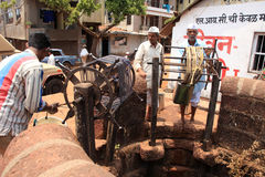 Villagers take water from a traditional public well Royalty Free Stock Images