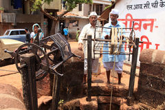 Villagers take water from a traditional public well Stock Image