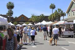 Many People Shop at a Farmers Market. The Villages, FL, USA -April 1, 2017: People shop at a farmer's market. Street market shops under canopies sell to royalty free stock photo