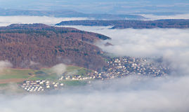Villages half under fog cover Stock Photography