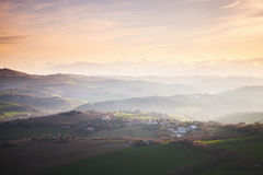 Villages and on hills under colorful cloudy sky, Italy Stock Photography