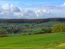 Villaggio alla valle con la crescita di raccolti intorno Immagini Stock Libere da Diritti