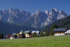 Villaggio in alpi con la cresta della montagna nella priorità bassa Immagini Stock Libere da Diritti