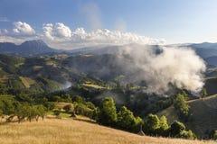 Villaggio alpino in montagne Fumi e foschia sopra le colline in Carpathians Fotografia Stock