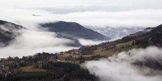 Villaggio alpino nella nebbia La Francia, rhone-Alpes Fotografie Stock