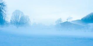 Villaggio alpino nella nebbia nell'inverno Fotografia Stock Libera da Diritti
