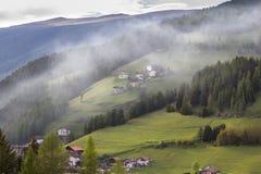 Villaggio alpino nelle nuvole della foschia Immagini Stock
