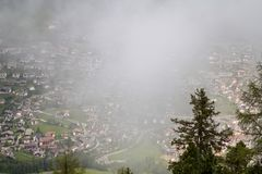Villaggio alpino nelle nuvole della foschia Immagine Stock