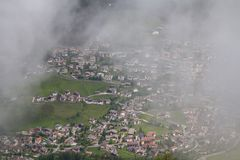Villaggio alpino nelle nuvole della foschia Fotografia Stock