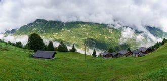 Villaggio alpino in nuvole nebbiose Immagine Stock