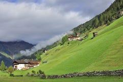 Villaggio in Austria con i prati inglesi e le montagne verdi Fotografie Stock