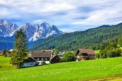 Villaggio austriaco fra i prati e le alpi verdi Fotografia Stock