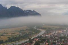 Villaggio con il fiume e montagna in foschia Fotografia Stock