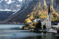 Villaggio con il fondo iconico della chiesa, del lago e della montagna fotografia stock libera da diritti