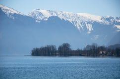 Villaggio con il lago ed il fondo delle alpi Fotografia Stock