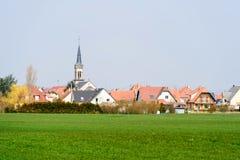 Villaggio con la chiesa ed il campo agricolo verde Immagine Stock Libera da Diritti