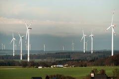 Villaggio davanti alla vista di panorama sopra il paesaggio del parco eolico in Germania con le turbine bianche del generatore Immagine Stock