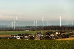 Villaggio davanti alla vista di panorama sopra il paesaggio del parco eolico in Germania con le turbine bianche del generatore Fotografia Stock