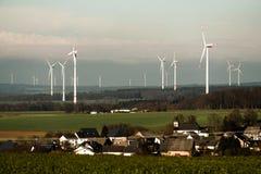 Villaggio davanti alla vista di panorama sopra il paesaggio del parco eolico in Germania con le turbine bianche del generatore Immagine Stock Libera da Diritti