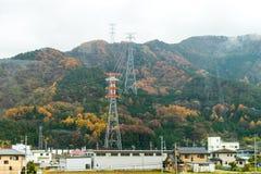 villaggio del paese e palo di alta tensione con il mapl di autunno del paesaggio Immagini Stock