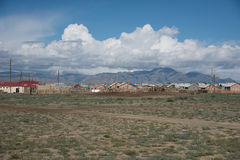 Villaggio di Altai nel deserto e cielo con le nuvole di estate Fotografia Stock