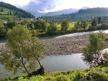 Villaggio di favola su un prato verde accanto ad un fiume basso con un'isola sparsa con le pietre Immagine Stock
