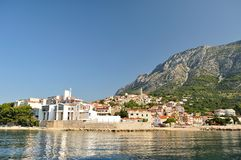 Villaggio di Igrane con la torre, il mare adriatico e l'alta montagna Biokovo nel fondo Fotografia Stock