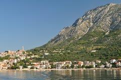 Villaggio di Igrane con la torre, il mare adriatico e l'alta montagna Biokovo nel fondo Immagine Stock Libera da Diritti