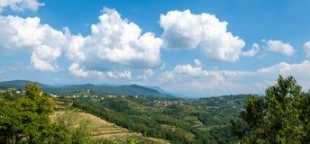 Villaggio di Kojsko, di regione viticola famoso di Sloveniain di Goriska Brda, acceso dal sole e dalle nuvole nel fondo, santo fotografia stock