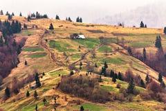 Villaggio di montagne sui pendii di collina Colline verdi in valle della montagna Immagine Stock