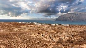 Villaggio di Pedro Barba sotto un cielo con le nuvole Oceano sui precedenti La Graciosa, Lanzarote, isole Canarie, Spagna Fotografia Stock