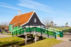 Villaggio di Zaanse Schans, l'Olanda, serre e mulini a vento contro il cielo nuvoloso blu Immagine Stock