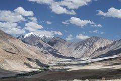 Villaggio a distanza in montagne del deserto del amoong della valle alte Immagine Stock