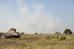 Villaggio e grassfires africani Fotografie Stock Libere da Diritti