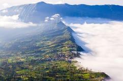 Villaggio e scogliera al vulcano di Bromo, Indonesia immagini stock libere da diritti