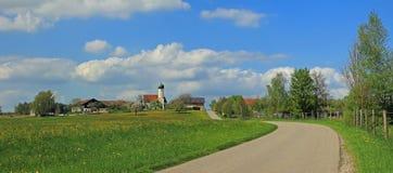 Villaggio idilliaco con la chiesa, paesaggio bavarese Immagine Stock
