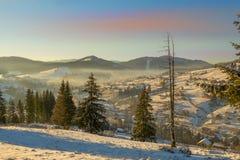Villaggio in montagne di inverno al tramonto Fotografie Stock Libere da Diritti