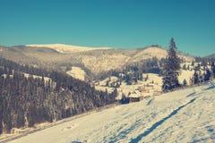 Villaggio nelle montagne coperte di neve al tramonto Fotografie Stock