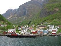 Villaggio norvegese a distanza su un fiordo Immagine Stock