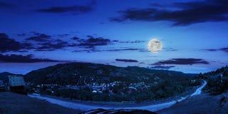 Villaggio sul pendio di collina della montagna alla notte Immagini Stock