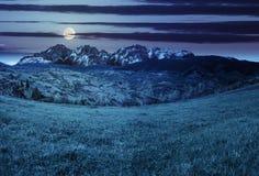 Villaggio sul prato del pendio di collina in alte montagne alla notte Immagini Stock