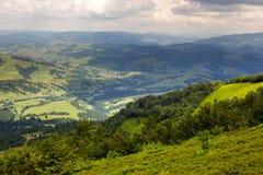 Villaggio sul prato del pendio di collina con la foresta in montagna Fotografie Stock Libere da Diritti