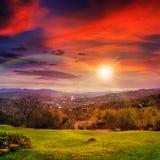 Villaggio sul prato del pendio di collina con la foresta in montagna al tramonto Fotografie Stock Libere da Diritti