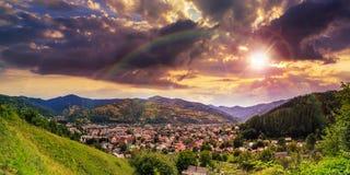 Villaggio sul prato del pendio di collina con la foresta in montagna al tramonto Immagine Stock