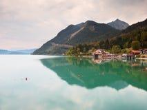 Villaggio sulla banca del lago alps I picchi di alta montagna in specchio di gren il livello dell'acqua Fotografie Stock