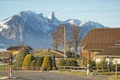 Villaggio svizzero in vista delle montagne delle alpi vicino alla La di Thun Fotografie Stock Libere da Diritti