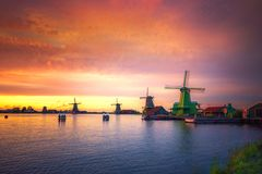 Villaggio tradizionale con i mulini a vento olandesi ed il fiume al tramonto, Paesi Bassi Immagini Stock Libere da Diritti