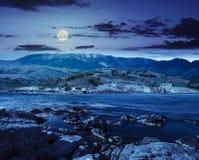 Villaggio vicino al lago in montagne alla notte Fotografie Stock