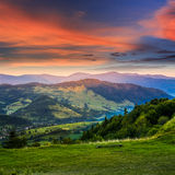 Villaggio vicino alla foresta in alte montagne ad alba Fotografie Stock Libere da Diritti