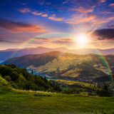 Villaggio vicino alla foresta in alte montagne al tramonto Immagine Stock Libera da Diritti